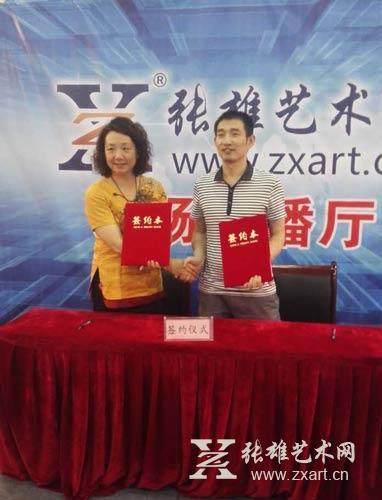上海朵云轩(集团)副总经理路燕(左)与张雄艺术文化有限公司董事长张雄(右)成功签约